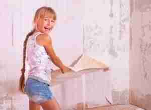Chica se divierte quitando papel pintado de la pared